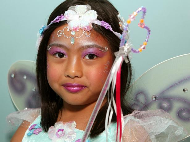 To apply fairy princess makeup, begin with a pearly eye shadow. Then add pink blush on the cheeks. Next, apply self-adhesive glittering jewels on forehead like a princess' tiara, and then apply additional jewels under eyebrows, on cheekbones or anywhere you like. Tip: You can find self-adhesive jewels in the scrapbooking section of your local craft store. Make sure your child doesn't have any adhesive allergies before continuing with this step. Keeping away from the sensitive eye area, dab face lotion on the cheeks and surrounding the jewel tiara on forehead. Have model close her eyes then apply cosmetic glitter where lotion was applied. Paint lips with a sparkly pink lipstick or tinted lip-gloss. Finish the look with a fairy princess costume.