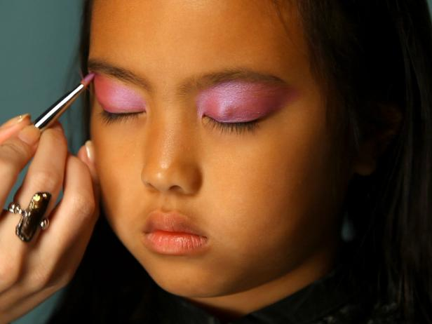 To apply fairy princess makeup, begin by painting eyelids with a pearly shade of eye shadow. Use a wet eye shadow for this, or shimmering face paint. Tip: Paint all the way up to eyebrows so the color is easily seen. Using a sponge or finger, blend a lighter shade of pearly eye shadow over and above eyebrows. Brush pink blush on apples of cheeks, continuing up to the highest point of cheekbones.