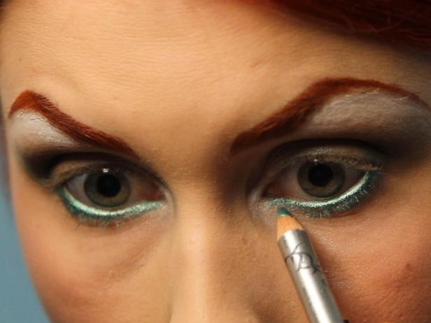 Line your waterline, which is the inside of your eyelid, with a shimmering green pencil liner. Extend the color even below the waterline onto your lash line, and make sure the green is vibrant.