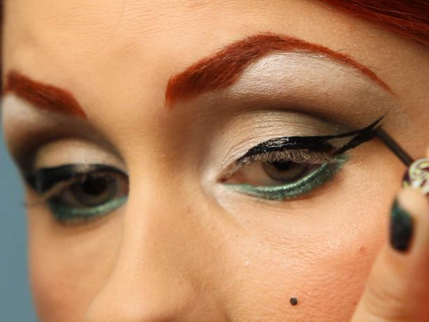 Use black liquid eyeliner to create a thick cat eye. Start at the center and wing out, then go back to the inner corners and connect the line all the way across your lid.