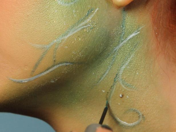Add some subtle dots with the white liquid liner for texture, then use green glitter liner to trace around the vines.