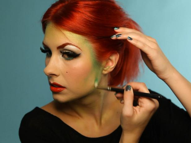 Begin to blend green eyeshadow around the edges of your face and in your cheek contour. Blend 2 to 3 shades of green in a gradient starting at your hairline, and working outward. Choose a deep forest green shade, a Kelly green and a lime shade; at least one of your shadows should have shimmer in it.