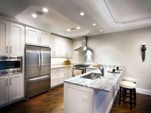 White Kitchen With Marble Countertops and Stainless Appliances
