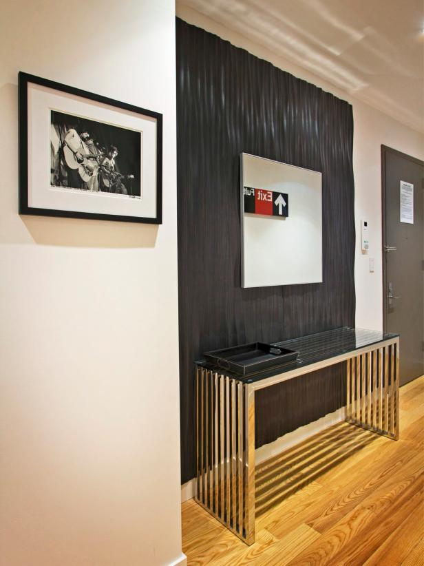 Entryway With Black Accent Wall, Glass Console Table, and Modern Art