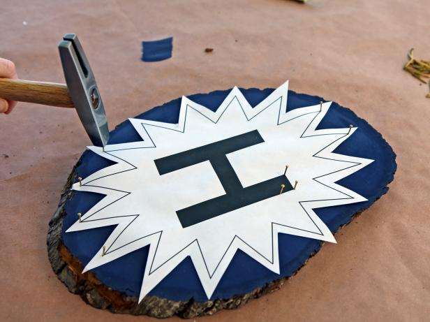 Center template onto plaque. Keep paper taut and start hammering nails into alternating points of the starburst. Continue adding nails approximately half an inch apart all around the outer edges of the starburst and letter.