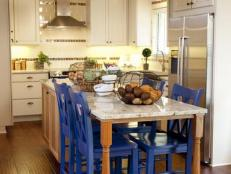 White Kitchen With Spacious Island and Blue Chairs