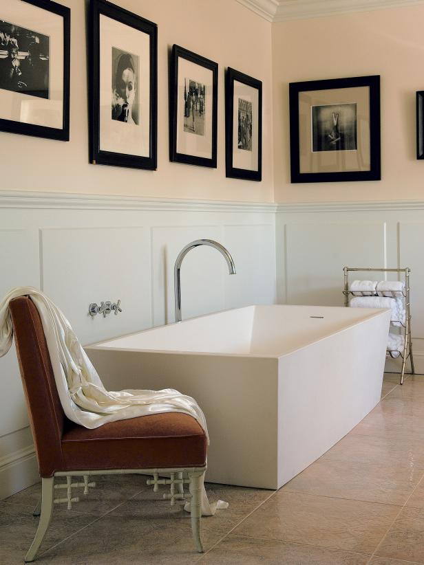 White bathtub with chair and photos on wall