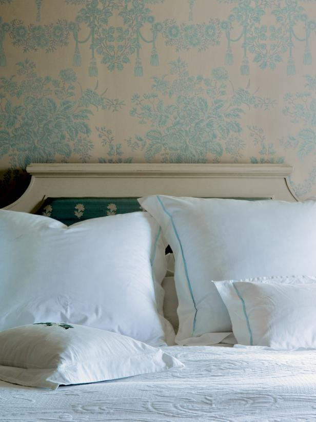 Blue Floral Wallpaper Above White Upholstered Headboard