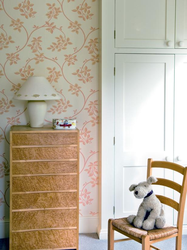 Girl's Bedroom With Floral Wallpaper and Wood Dresser