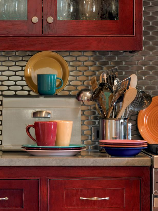 Warm Red Cabinets, Colorful Dishes, Stainless Steel Backsplash
