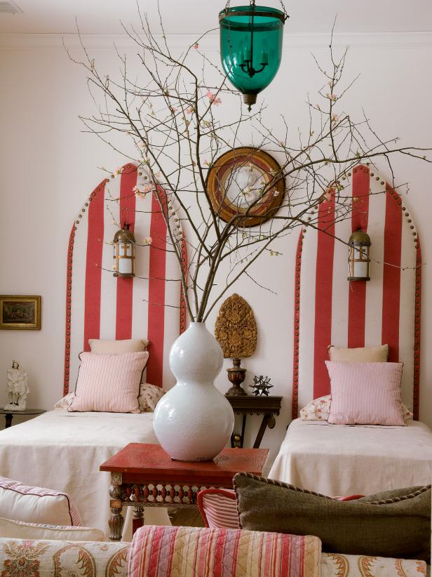 Bedroom With Red and White Striped Twin Beds and Tree Branches in Vase