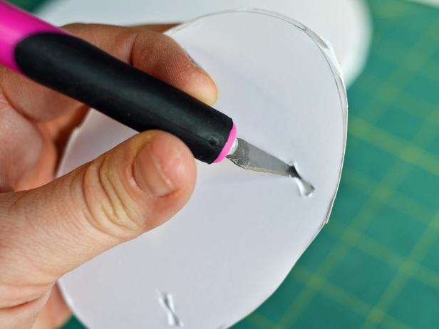 After cutting the ribbon piece in half, Step 2B is to punch four holes into one of the smaller foam core ovals using a craft knife.  The holes should be in the shape of a square. The ribbon can then be threaded through the cut-outs