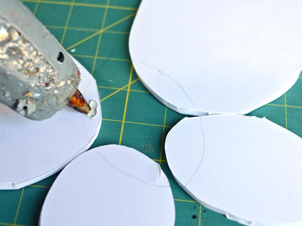After tracing the oval with the ribbon strap over the center of the other arranged ovals, Step 3B in making feathered angel wings is to remove the ribbon strap oval. Apply hot glue inside the traced area.