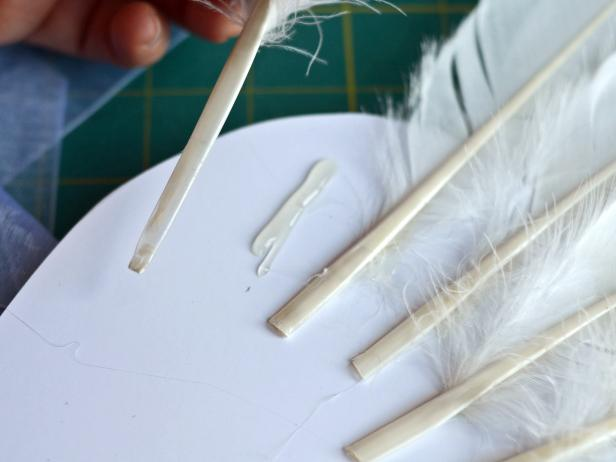Step 5 in creating angel or fairy wings is to apply hot glue to a foam core board, a couple of inches below the area where feathers were inserted in Step 4.