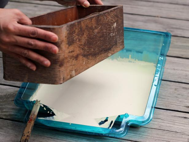 Step 3 in crafting a chic bathroom caddy is to dip the bottom of a wooden box into a pan of paint. Repeat several times until you get the perfect amount of paint on the bottom of the box. Allow the box to dry.