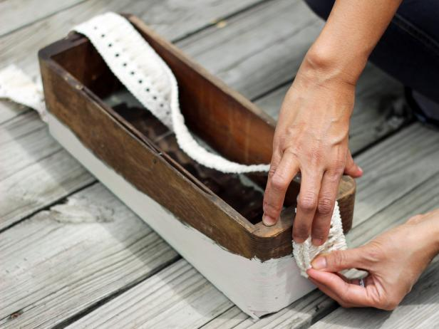 Step 4 in crafting a chic bath caddy for guests is preparing to fasten the fabric tape, cut to length, to each side of the painted and dry wooden box. Eventually the trim will be fastened to a doorknob with a nut and bolt.