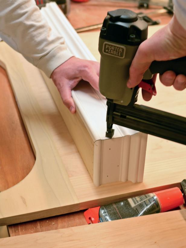 After dry-fitting the pieces together for a custom range hood project, the front and sides of the shelf can be nailed into place using a finishing nailer. Line the pieces up and hold them tightly during the attaching process.