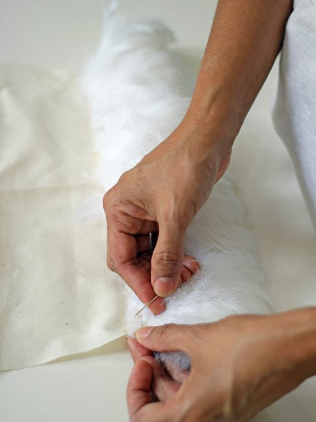 Step 4A in embellishing a vanity chair with feathers is to begin sewing strips of fabric onto the muslin fabric shape. Beginning at the top of the fabric, sew lengths of feathers across the fabric and continue rows from top to bottom.