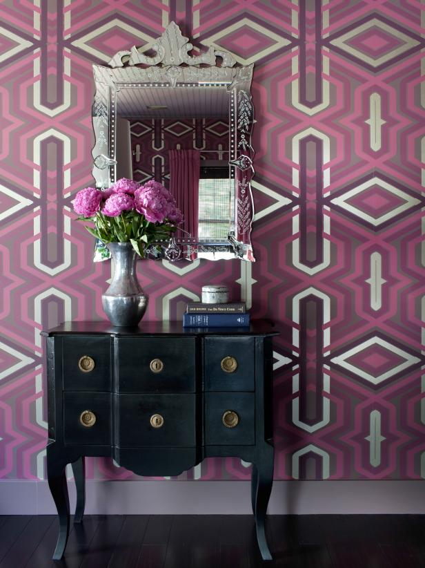 Black Dresser and Ornate Mirror Against Plum & Fuchsia Patterned Wall