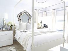 All-White Bedroom With Multifaceted Geometric Mirror