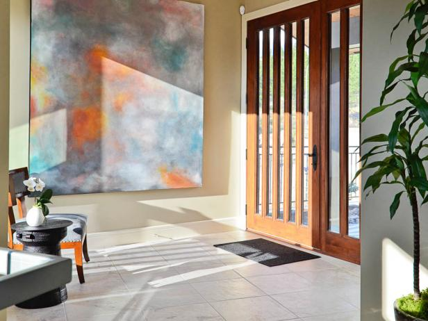 Transitional Entryway With Colorful Artwork and Detailed Wooden Door