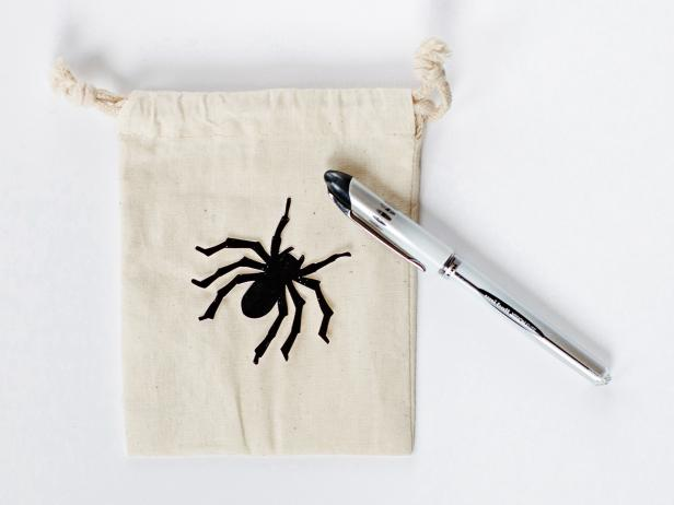 Using scissors, cut carefully around design's outside edge to create a pattern. Lay pattern on muslin bag, and using a pen or pencil, carefully trace around outside.