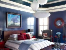 Bold Blue Master Bedroom With Red Accents and Abstract Art