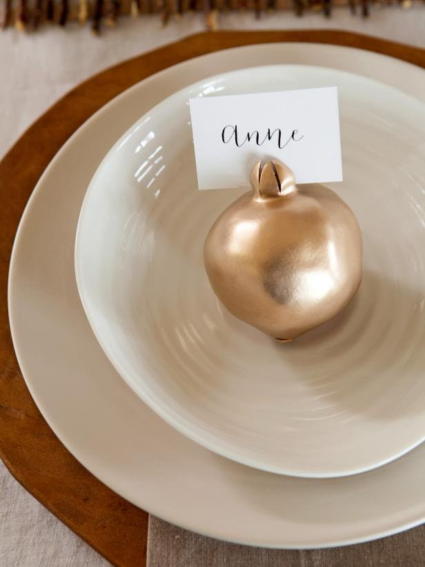 Keep your dinner drama-free and avoid a game of musical chairs by setting out place cards for your guests. For a look that's both seasonal and sleek, make these gilded place-card holders by spraying pomegranates with metallic paint, then inserting a handwritten place card in the crown. Inexpensive and homemade, they're the perfect way to make your place setting feel extra special. Get step-by-step instructions: http://www.hgtv.com/handmade/how-to-make-pomegranate-place-card-holders/index.html