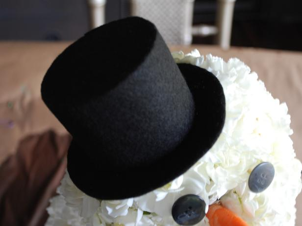 Use hot glue gun to secure wooden skewer inside a doll-sized top hat. Place hat on top of the 4-inch sphere until securely held in place with attached skewer.