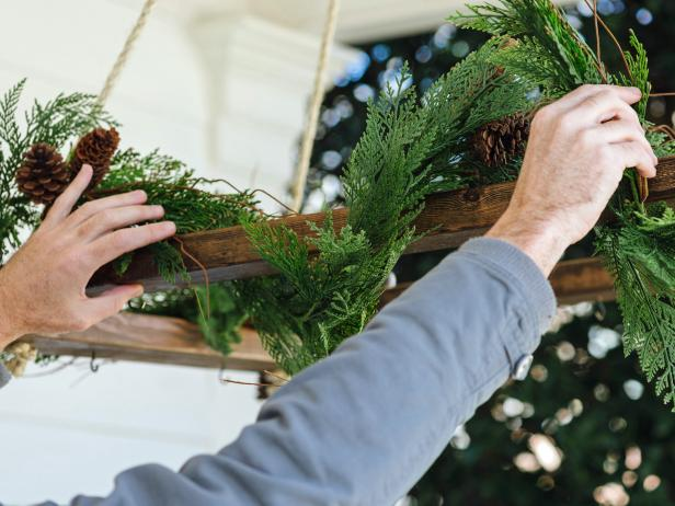 Gather fallen branches with greenery from the yard, or pick up bundles of Christmas tree trimmings from a local Christmas tree lot. Layer trimmings along the top of the chandelier frame, securing them in place with galvanized wire.