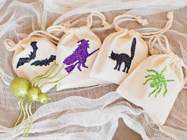 Plain fabric bags are transformed into kid-pleasing Halloween party favors with paint and glitter in the shape of a spooktacular design.