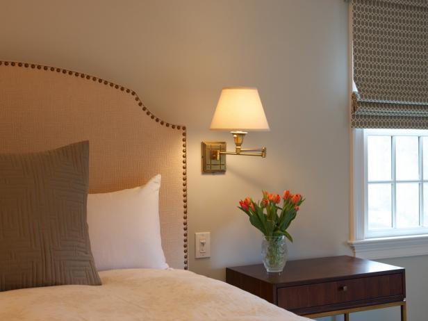 Nailhead Upholstered Headboard & Wall-Mounted Lamp in Neutral Bedroom