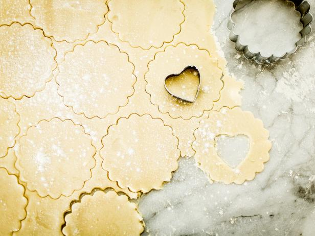 Using a 3-inch fluted round cookie cutter, cut out 3 dozen circles. On only half of the rounds, use a 1-inch heart-shaped cookie cutter to cut out centers; these will be the tops of the finished cookies.