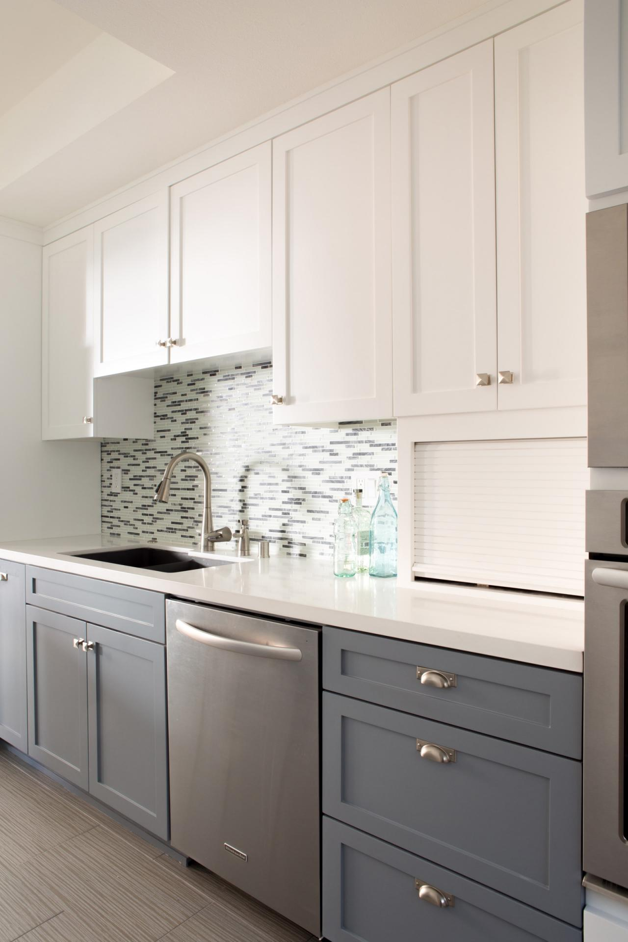 sleek two toned kitchen cabinets light plays off the glass tile