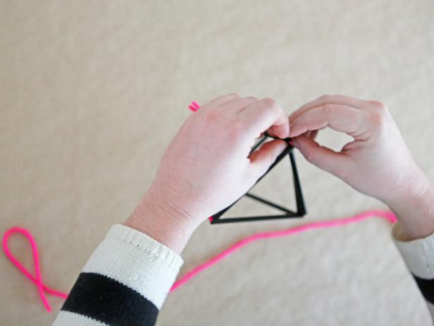 Step 7: Using a second length of string, tie the two side triangles together underneath to finish the diamond shape.