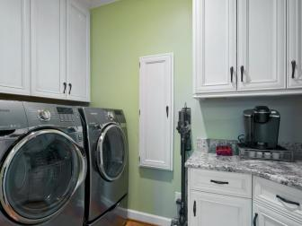 Traditional Green Laundry Room With White Cabinetry