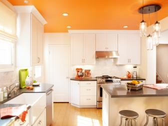 Contemporary Orange and White Kitchen With Eat-In Island