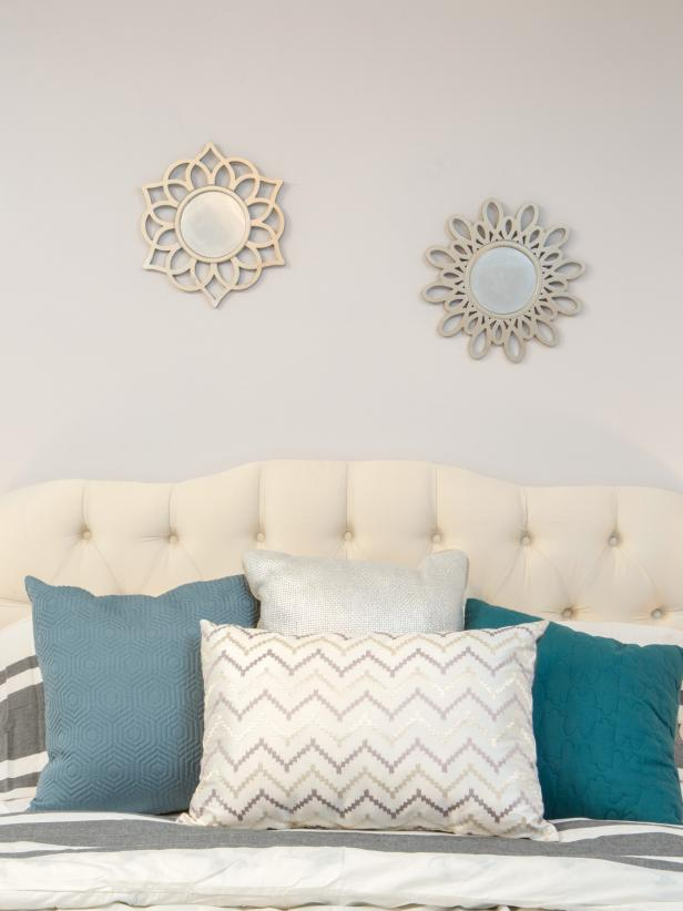 Teal & Chevron Pillows Propped Up Against White Tufted Headboard