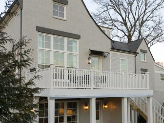 White Painted Brick Home Exterior With Two-Story Deck
