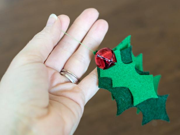 Pinch together 2-3 holly leaves for the cat toy of varying colors and shapes. Use green thread on an all-purpose sewing needle to secure leaves together at the top. Make sure stitch is strong, so leaves aren't easily pulled away during kitty's playtime. Once leaves are secure, use same thread to tack on two red bells, again, making sure they are secure.