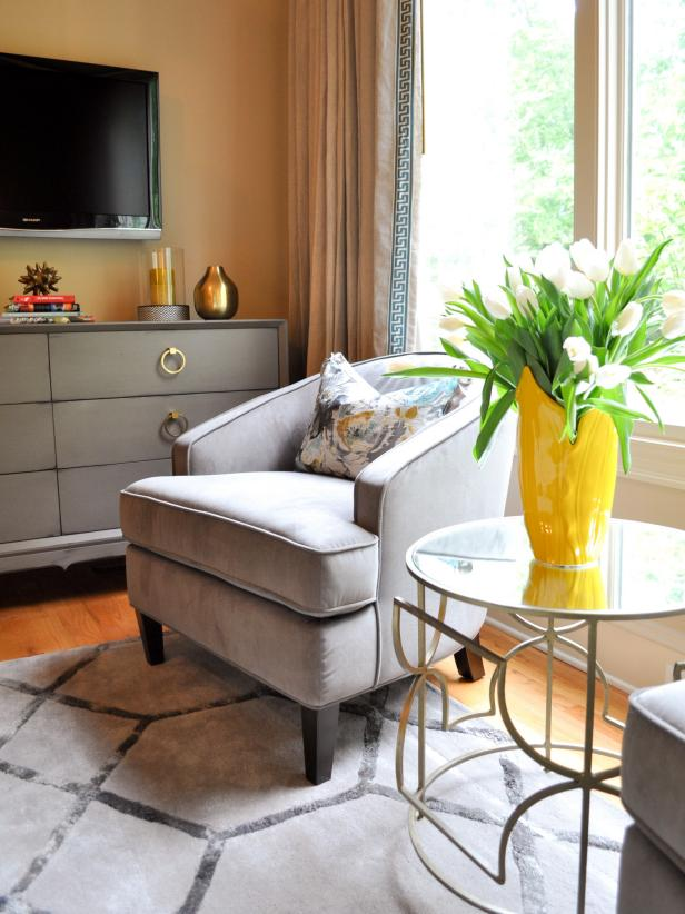 Grey and beige transitional bedroom seating area with a yellow vase.