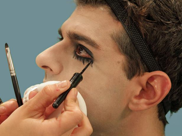 Use black liquid eyeliner to draw random vertical tear lines from the bottom eye. Use a flat brush to blend while the liner is still wet
