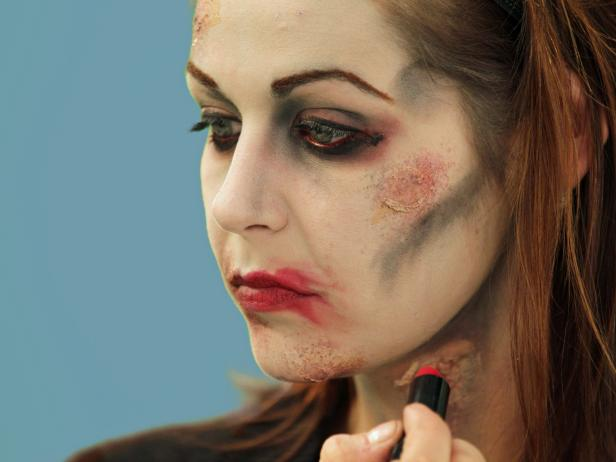 Complete your Halloween zombie look with detail work. Add a few dots of red lipstick then smear it out and away from the lips.