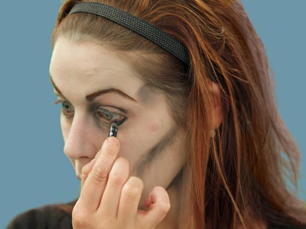 To create the eyes of the undead, line the eyes using black eyeliner on the top and bottom in a heavy, uneven pattern.
