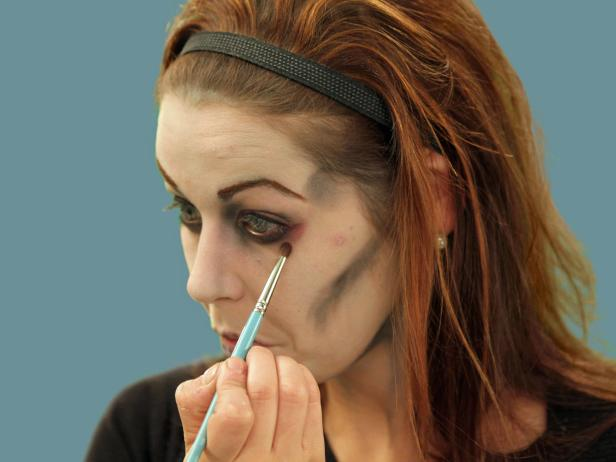 With an eye shadow brush, add some red blush near the eye and a red eye liner to the water line of the eye. This will make the zombie eyes appear tired and sickly.