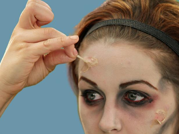 Use liquid latex to make your zombie face even scarier and create fake scars. Apply thin, dime-sized layers in various shapes and sizes on your cheek, forehead and chin. The texture gets tacky in about 20 seconds and can be pulled a little off the face to look like decaying skin.