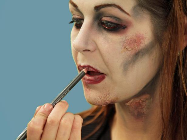 To complete your zombie look, add red coloring to the lips. Randomly add some red lip liner to the inner lips, but don't cover the black, detail lip lines.