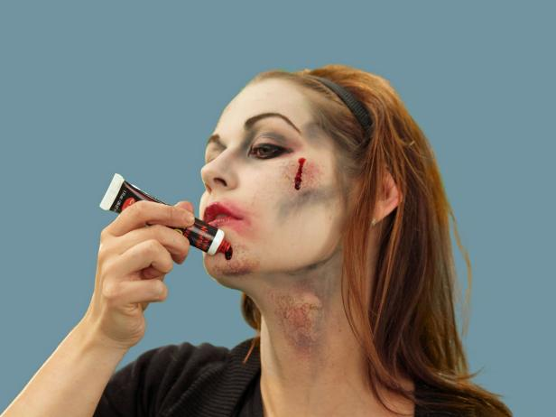 To complete the zombie Halloween look, add drips of stage blood to selected areas around the face and neck.