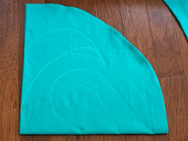 Fold turquoise felt into quarters and sketch a large, simple design in chalk onto felt. Note: This design will be cut out as the felt is still folded, creating a symmetrical design, similar to a paper snowflake.
