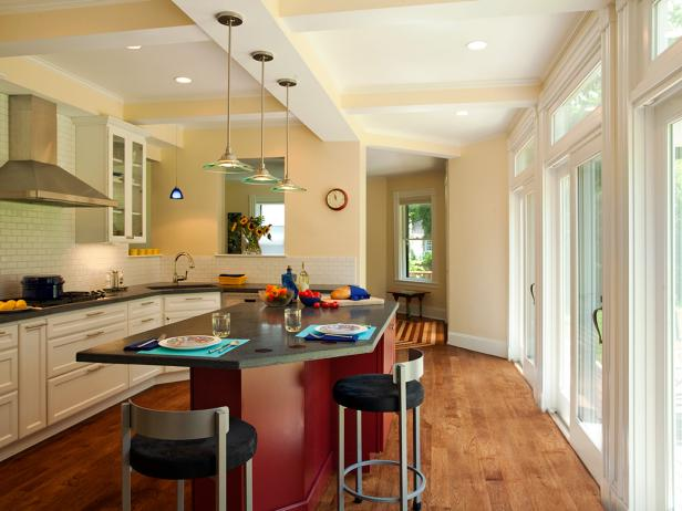 Neutral Kitchen With Red Island, Dark Countertops and Glass Pendants